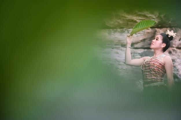 葉緑葉フィルター、タイのアイデンティティ文化を通して見る伝統的なタイの衣装でタイの女の子。 Premium写真