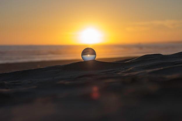 日没で砂の上に腰掛けて水晶球 Premium写真