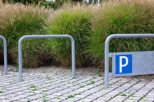 青い駐車標識と空の自転車駐車場。 Premium写真