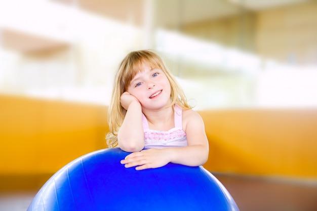 Маленькая девочка с мячом для аэробики Premium Фотографии