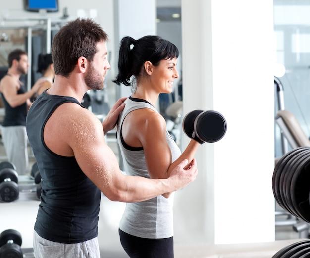 ウェイトトレーニングを持つジム女性パーソナルトレーナー Premium写真