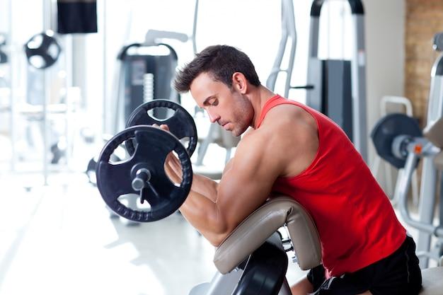 スポーツジムでウエイトトレーニング機器を持つ男 Premium写真