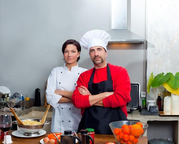 シェフカップル男性と女性が台所でポーズをとる Premium写真
