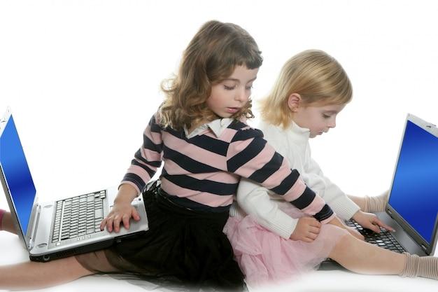コンピューターのラップトップと二人の少女姉妹 Premium写真