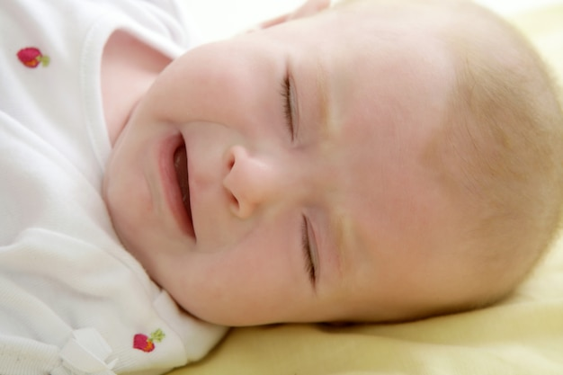 ベッドの上に敷設泣いている悲しい赤ちゃん Premium写真