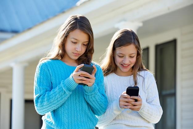 テクノロジースマートフォンを楽しんでいる姉妹双子 Premium写真