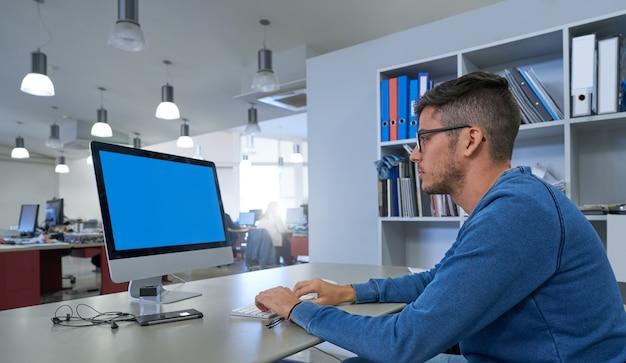 デザイナーの若い男がコンピューターで作業して Premium写真