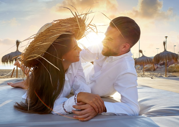 ビーチラウンジの夕日に若いカップル Premium写真