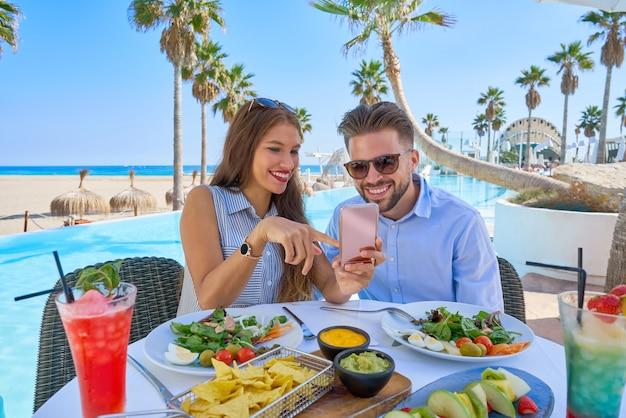 スマートフォンとプールレストランで若いカップル Premium写真