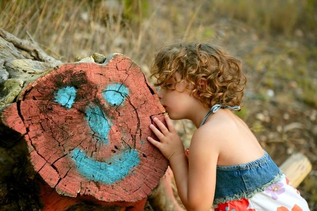 女の子が幸せそうな顔で刈り取らトランクを描く Premium写真