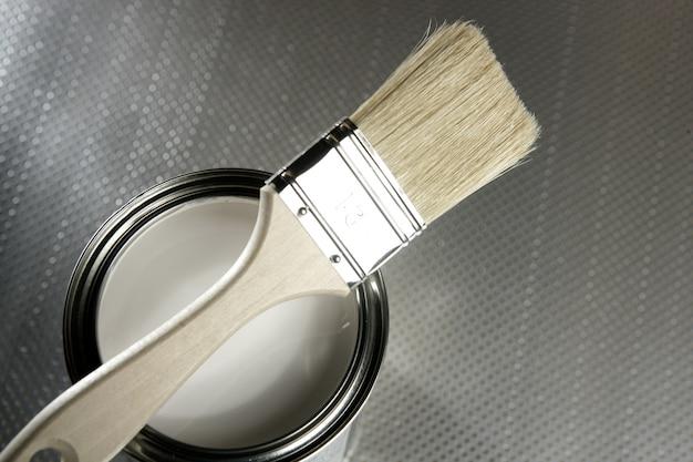 画家のブラシと白いペンキの錫 Premium写真