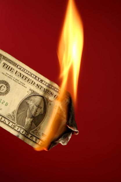 赤の上の火で燃えているドル紙幣 Premium写真