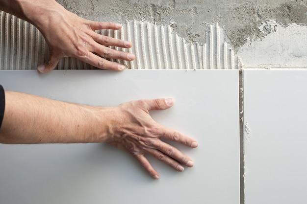Строитель каменщик руки на плитку работы Premium Фотографии