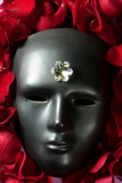 Черная карнавальная маска с лепестками красной розы Premium Фотографии
