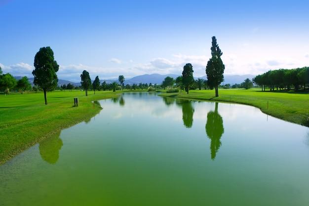 ゴルフ場の緑の芝生フィールド湖の反射 Premium写真