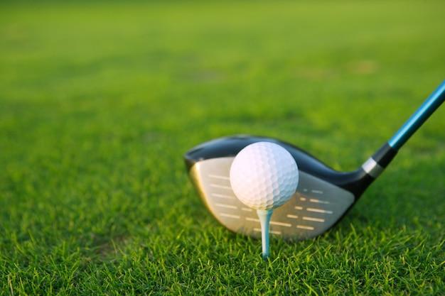 緑の芝生コースのゴルフティーボールクラブドライバー Premium写真