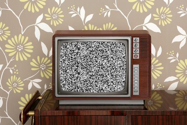 ヴィンテージの木製の壁にレトロな木製テレビ Premium写真