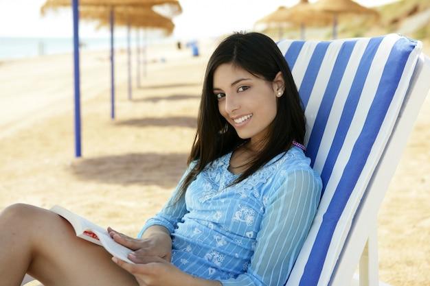 ビーチでリラックスした本を持つ美しい女性 Premium写真