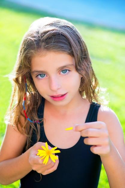 黄色のデイジーの花びらと愛をテスト子供女の子 Premium写真