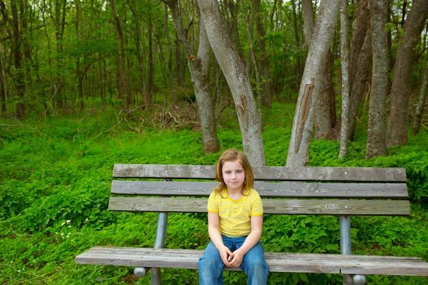 孤独な子供女の子幸せな公園のベンチに座っています。 Premium写真