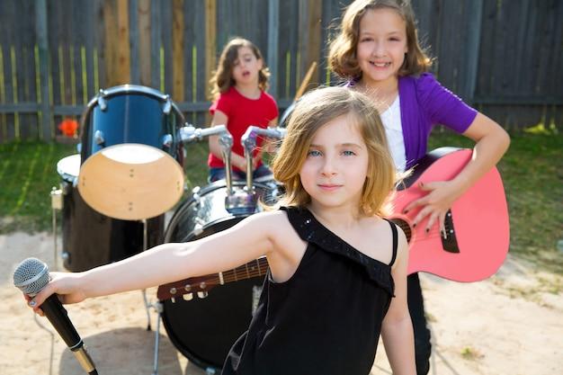 裏庭でライブバンドを演奏歌っている子供歌手の女の子 Premium写真