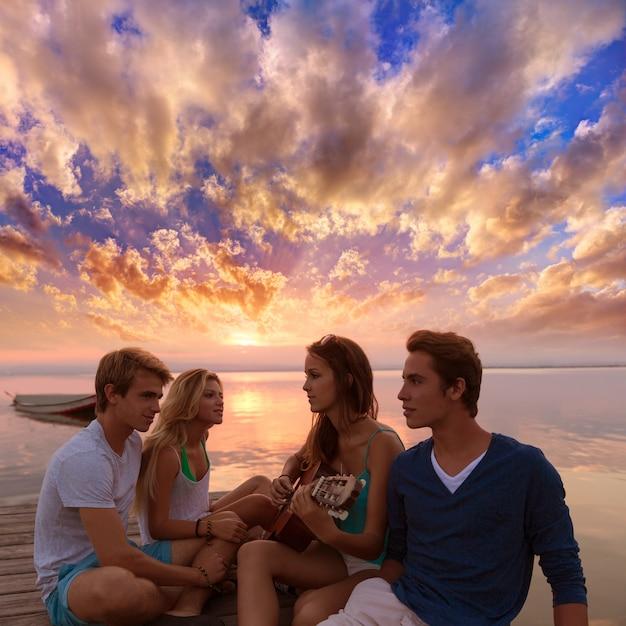 サンセットビーチでギターを楽しんで友達グループ Premium写真