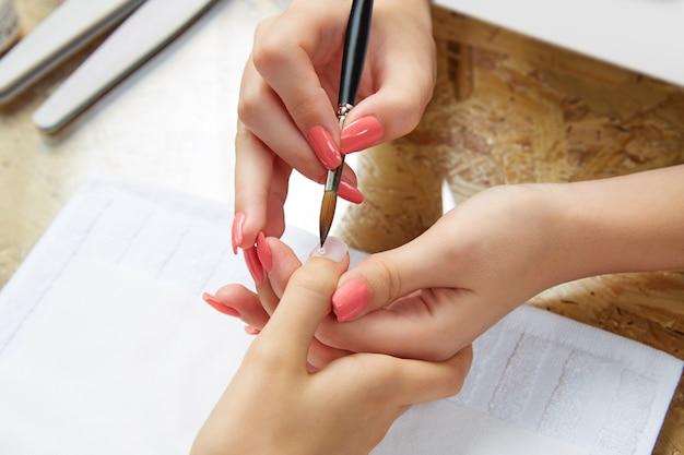 ネイルサロンでブラシを持つ女性絵画爪 Premium写真