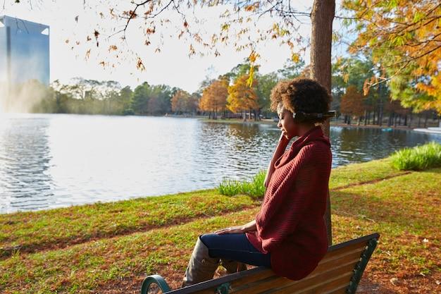 秋の公園で音楽を聴く女性 Premium写真