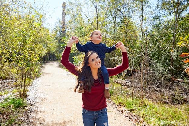 子供男の子が公園を歩いて母親の肩の上に座る Premium写真