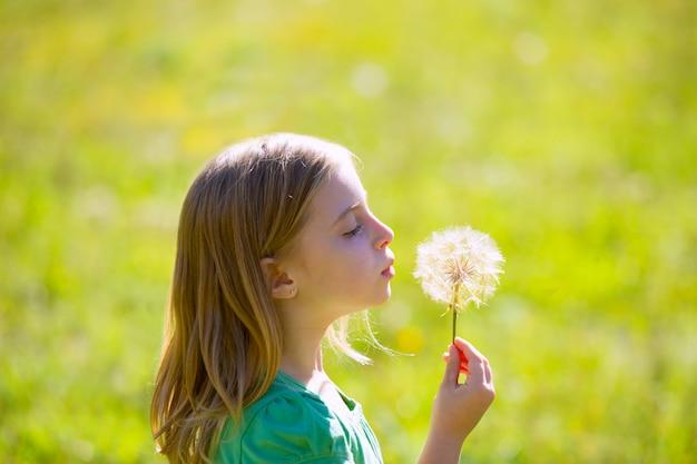 金髪の子供女の子緑の牧草地にタンポポの花を吹く Premium写真