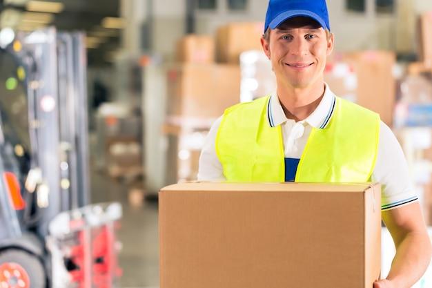 Работник держит пакет на складе экспедирования Premium Фотографии