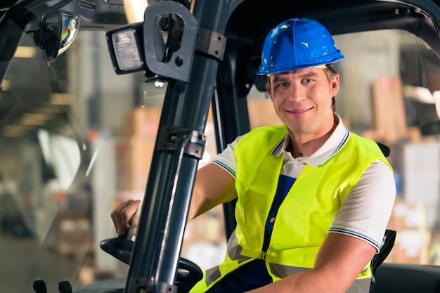 貨物運送会社の倉庫の保護ベストとフォークリフトのフォークリフト運転手、 Premium写真
