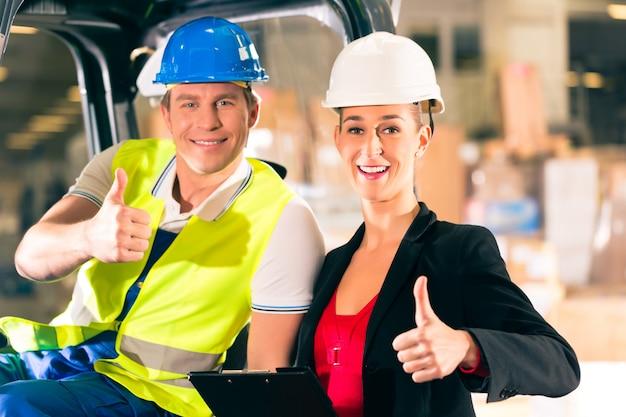 フォークリフトのドライバーと貨物運送会社の倉庫でクリップボードを持つ女性のスーパーバイザー、親指 Premium写真