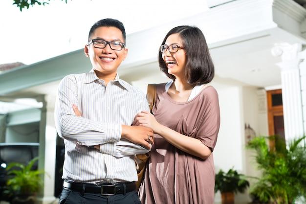 Азиатская пара домовладельца перед домом Premium Фотографии