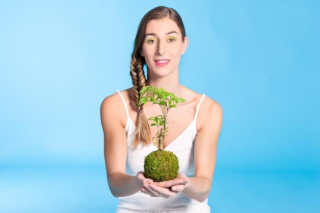 小さな木を保持している若い女性 Premium写真