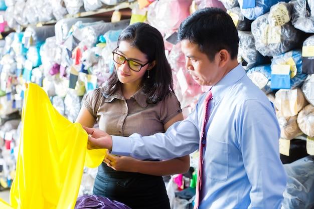 布を選ぶ倉庫のアジアの同僚 Premium写真