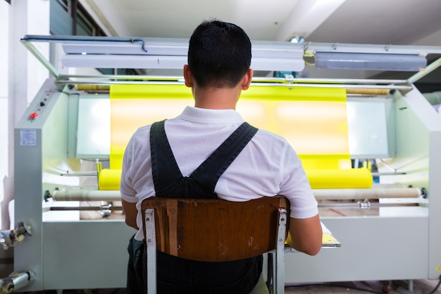 アジアの労働者は、織物工場で生地を制御します Premium写真