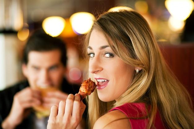 ファーストフードを食べるレストランのカップル Premium写真