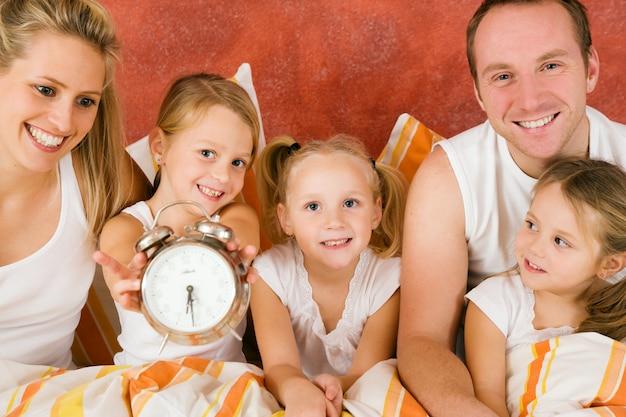 家族とベッドで朝食を持っている猫 Premium写真