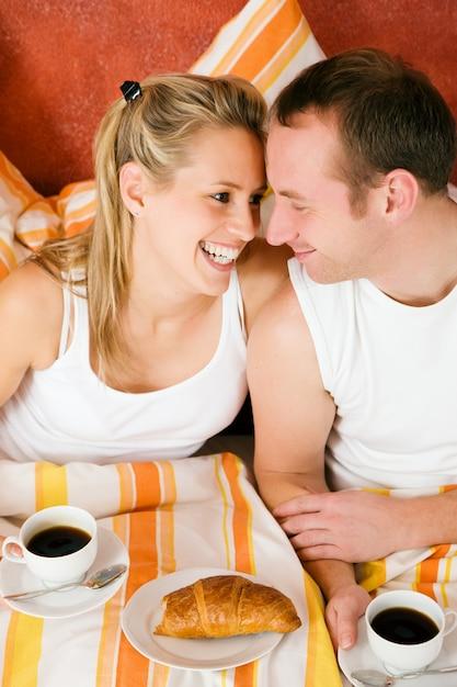 朝ビーズでコーヒーを飲むカップル Premium写真