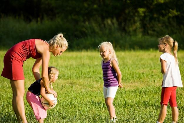 芝生のフィールドでサッカーをしている家族 Premium写真