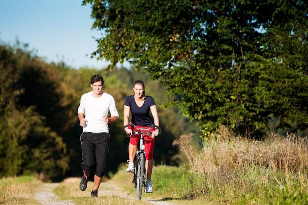 Молодая спортивная пара бегает и катается на велосипеде Premium Фотографии