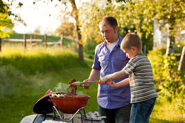 Семья устраивает барбекю в своем саду Premium Фотографии