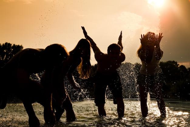 太陽に対して水で遊ぶ女の子のシルエット Premium写真