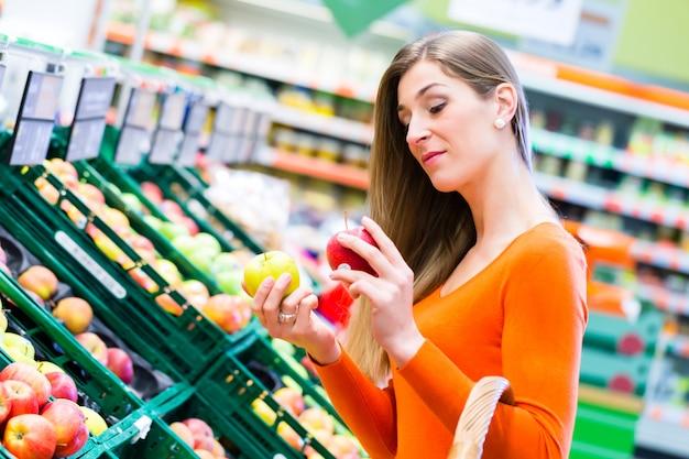 スーパーマーケットで果物を選択する女性 Premium写真