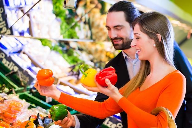 スーパーマーケットで野菜を選ぶカップル Premium写真