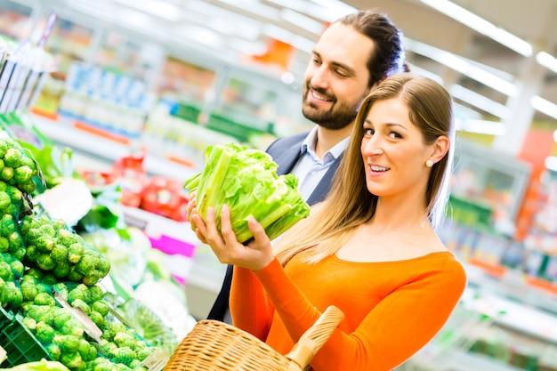 スーパーで食料品を買うカップル Premium写真