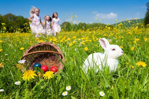 Дети на пасхальном яйце охотятся с кроликом Premium Фотографии