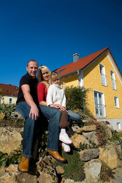 Семья позирует перед домом Premium Фотографии