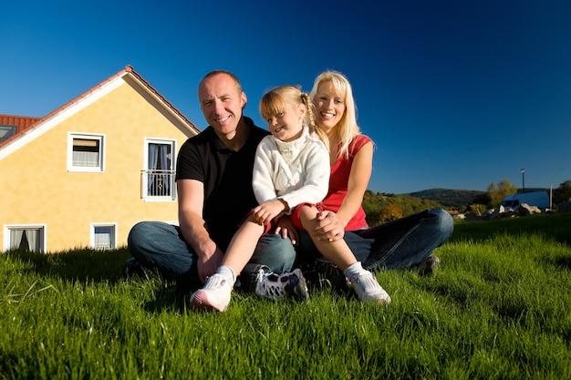Семья позирует перед их домом Premium Фотографии